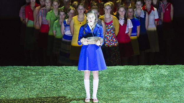 Ein Maedchen in einem blauen Kleid steht auf einer Buehne vor einem Maedchenchor.