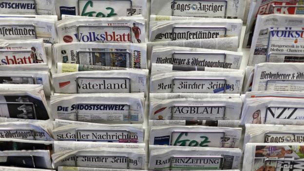 Zeitungen im Zeitungständer an einer Wand.