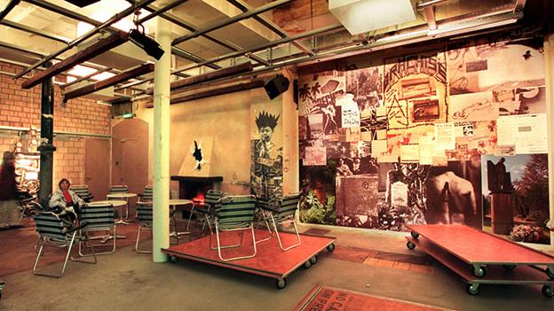 Ein Raum mit grossen Bildern an den Wänden.