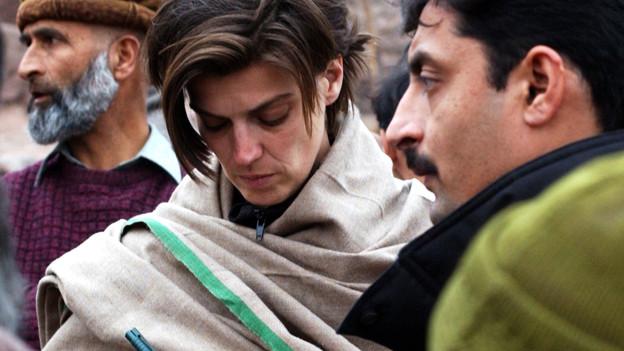 Carolin Emcke in ein Tuch gewickelt inmitten mehrerer Männer.
