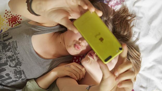 Zwei Mädchen fotografieren sich mit einem Smartphone selbst