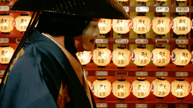 Eine japanische Theaterfigur geht an vielen Lämpchen, die zum Verakuf stehen, vorbei.