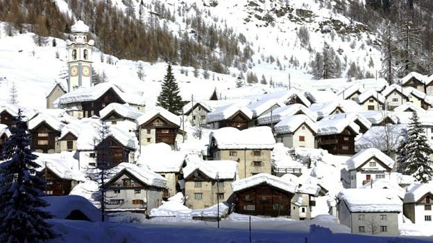 Blick auf das verschneite Dorf Bosco Gurin.