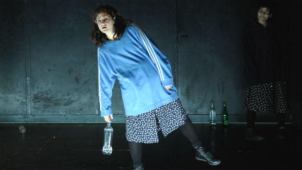 Suna Gürler auf der Bühne. Sie hat einen blauen Pullover an und eine Brille auf und trägt eine Flasche Wasser.