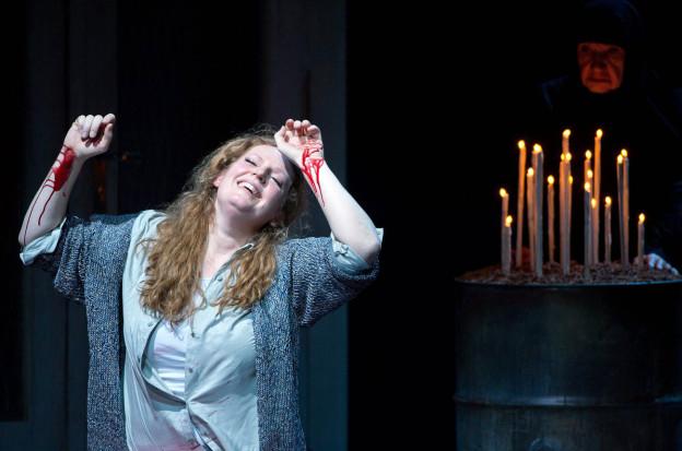 Eine Frau auf der Bühne: Blut an den Handgelenken, im Hintergund zahlreiche Kerzen.