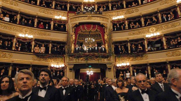 Ein Blick auf einen Opernsaal voller elegant bekleideter Menschen.