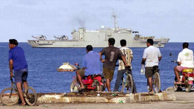 Flüchtlinge beobachten ein Kriegsschiff.