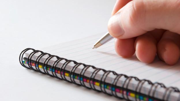 Hand mit Stift schreibt auf Block