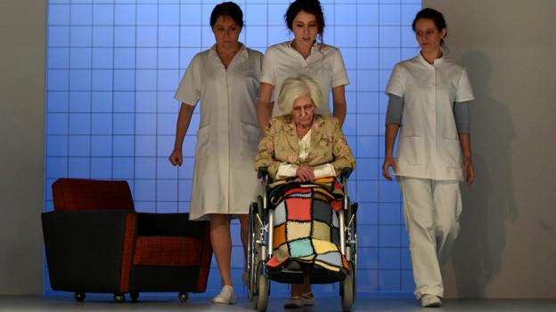 Pflegerinnen schieben Rollstuhl mit alter Frau
