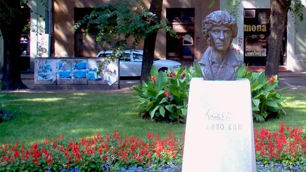 Büste von Danilo Kiš auf einem hellen Steinsockel, von Blumenbeeten gesäumt in einem Park verortet.