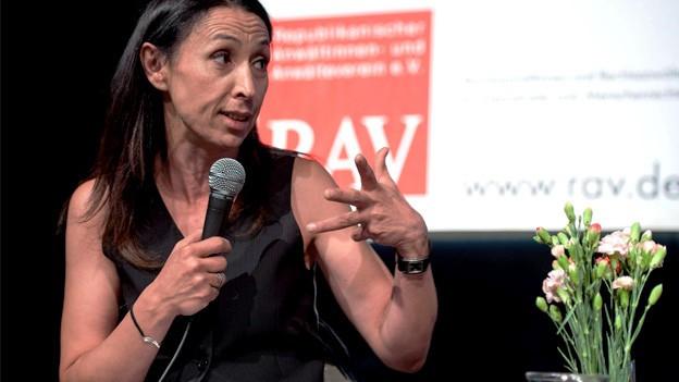 Shermin Langhoff debattiert an einer Pressekonferenz mit einem Mikrofon in der Hand.