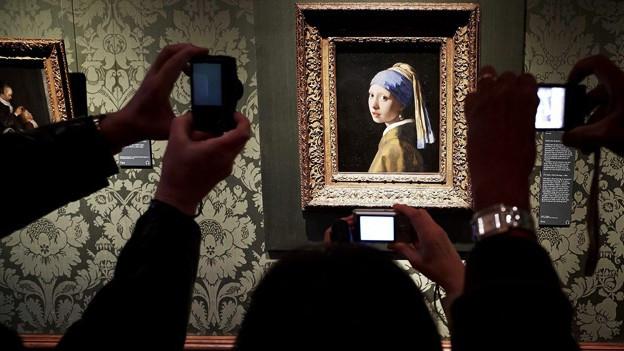 Vermeers Gemälde «Das Mädchen mit dem Perlenohrgehänge» wird von Besuchern eines Museums fotografiert.