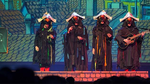 Vier zu Vögeln kostümierte Schnitzlebänggler stehen auf einer Bühne. Das Bühnenbild im Hintergrund zeigt die gemalten Dächer der Stadt Basel. Einer der vier Kostümierten spielt Gitarre.