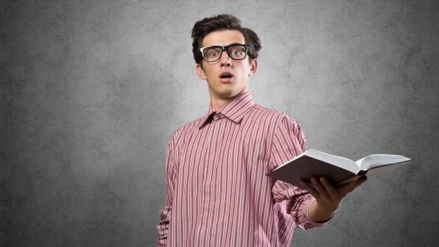 Ein Mann trägt eine Brille und hält ein Buch in der Hand.