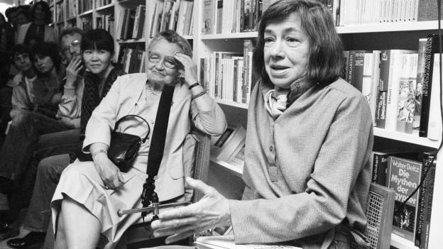 Eine ältere Frau sitzt vor einem Bücherregal und spricht, ein Buch auf dem Schoss. Neben ihr sitzen ältere Frauen, die ihr zuhören.