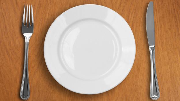 Ein leerer, weisser Teller mit Besteck.