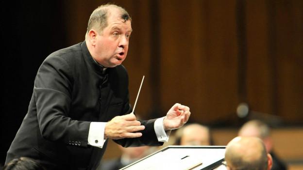 Ein Mann dirigiert ein Orchester.