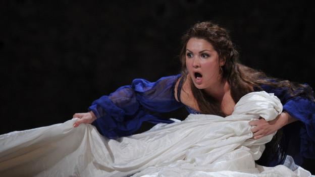 Die Sängerin Anna Netrebko beugt sich auf der Bühne über ein zerknülltes weisses Laken.