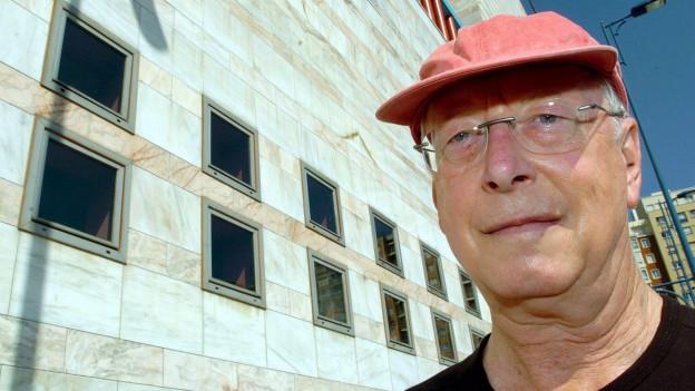 Musiker William Christie mit roter Mütze und randloser Brille.