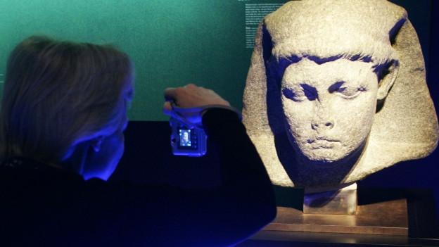 Frau steht mit Kamera vor einer ägyptischen Büster