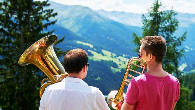 Zwei Männer mit Instrumenten blicken auf ein Bergpanorama.