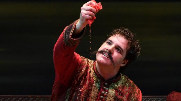 Mauro Peter mit Schnauz und exotischem Kostüm auf der Bühne.