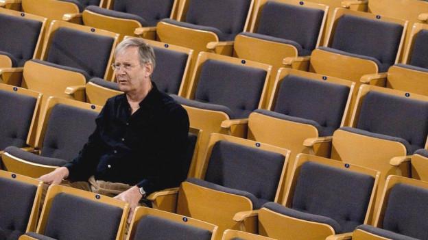 John Eliot Gardiner sitzt auf einem Stuhl in einem Kontertsaal.
