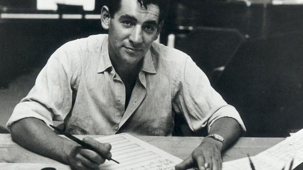 Leonard Bernstein schreibt auf ein Notenblatt