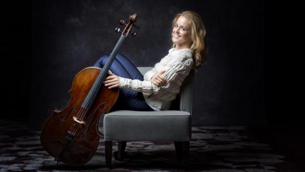 Eine Frau sitzt auf einem Sessel und hält ein Violoncello