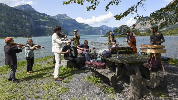 Menschen musizieren am Ufer eines Sees