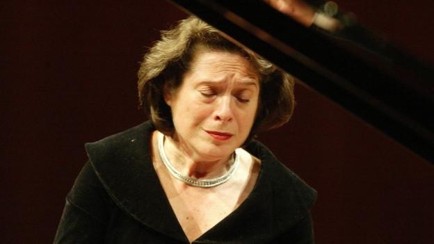Eine Frau sitzt mit geschlossenen Augen am Klavier