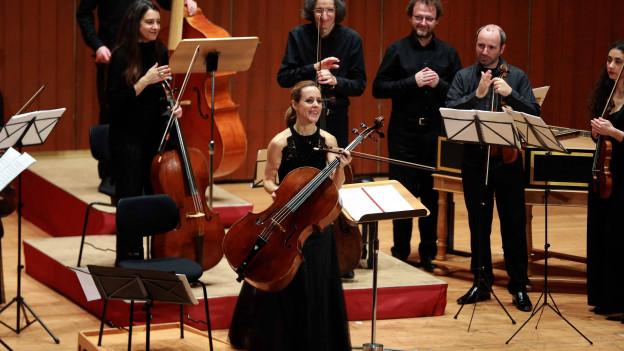 Frau steht auf einer Bühne vor einem Orchester und hält Cello in der Hand