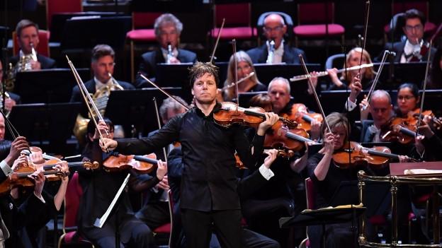 Ein Geiger steht mit ausgebreiteten Armen vor einem Orchester