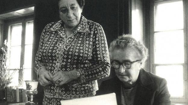 Schwarz-Weiss-Aufnahme: Zwei Frauen an einem Schreibtisch.