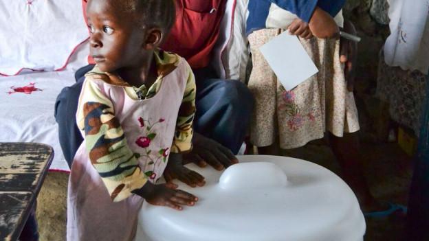 Eine Frau und ein Kind mit einer Mosan-Toilette, die aus einem Toilettenring und einem Eimer besteht.