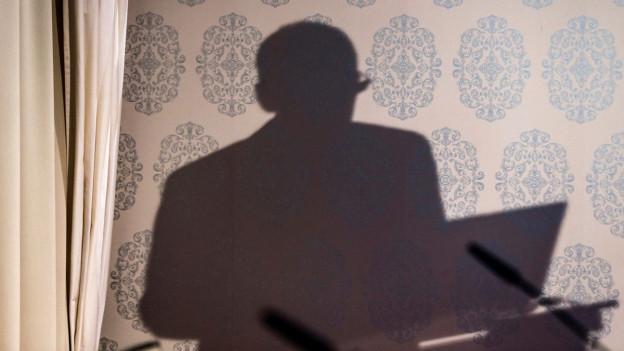 Der Schattenwurf eines Mannes auf einer Tapete.
