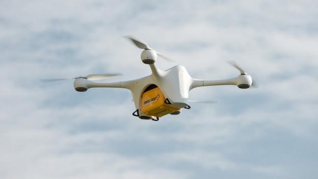 Eine Drohne transportiert ein gelbes Post-Paket.