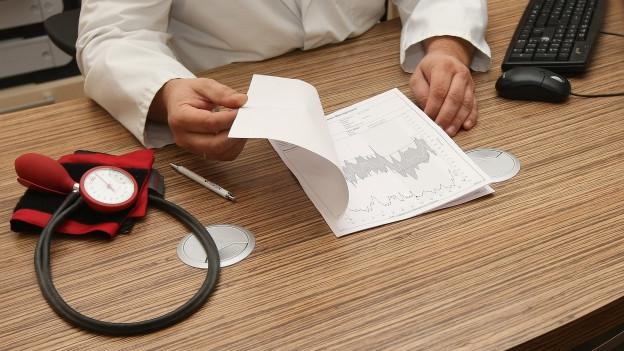 Der Tisch eines Arztes mit Bluthochdruck-Gerät darauf.