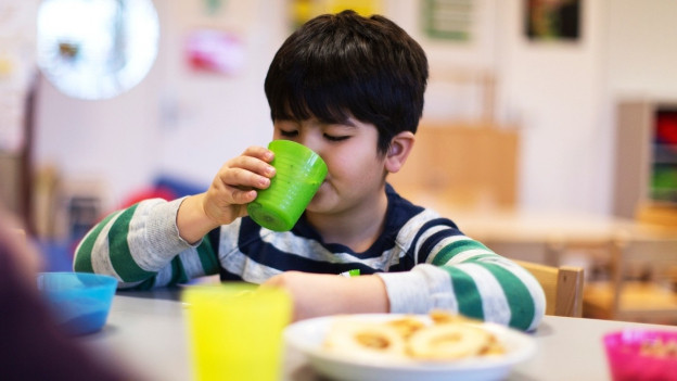 Ein Bub mit schwarzen Haaren trinkt aus einem Becher.
