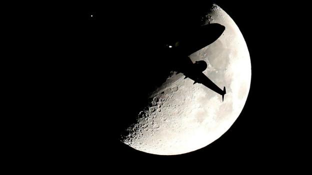 Ein Flugzeug wirft Schatten auf den Mond.