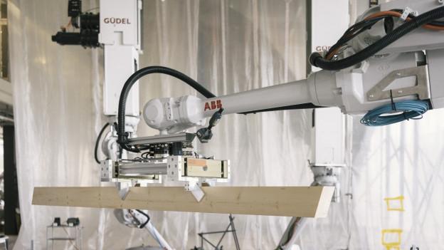 Ein grosser Roboterarm greift einen Holzbalken.