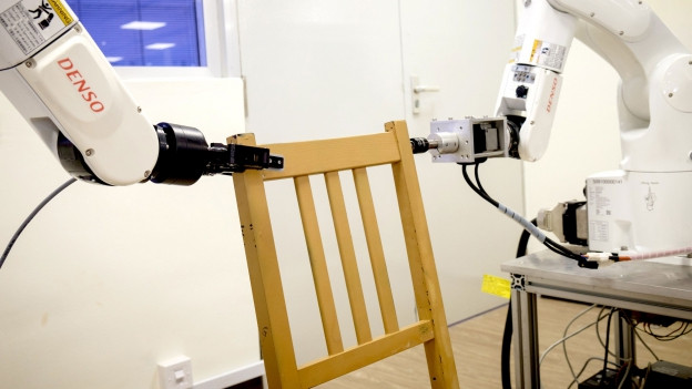 Roboter setzen einen Stuhl zusammen.