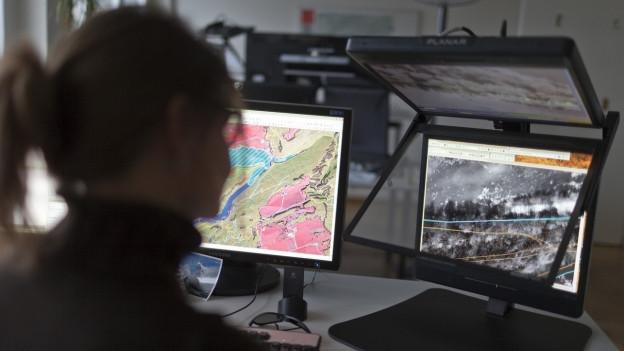 Eine Frau sitzt vor zwei Bildschirmen, auf beiden sind Karten abgebildet.