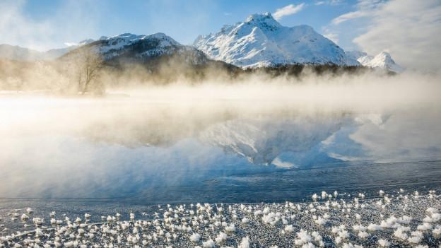 Winterliche Landschaft: Ein Berg im Schnee, davor ein gefrorener See, über dem wenig Nebel hängt, Eisblumben verzieren die Eisoberfläche