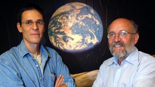 Zwei Herren, zwischen Ihnen ein Abbild eines Planeten
