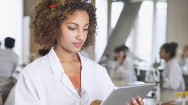Eine Frau blickt in einem Labor auf ihr Tablet