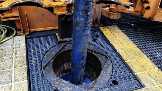 Geothermie-Bohrung mit Sicht auf eine dicke, blaue Stange, die in den Boden geht