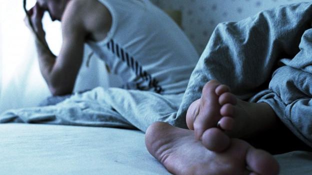 Mann sitzt frustriert auf dem Bett, auch im Bild: Frauenfüsse