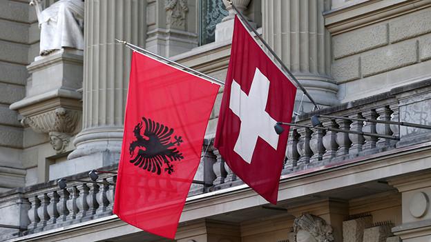 Die Flaggen Albaniens und der Schweiz wehen an der Fassade des Bundeshauses.