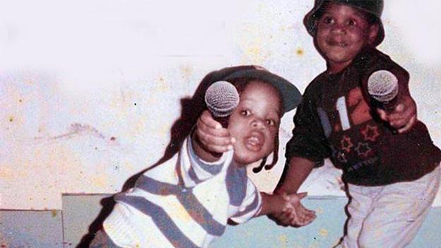 Zwei Buben mit Mikrofonen in der Hand.